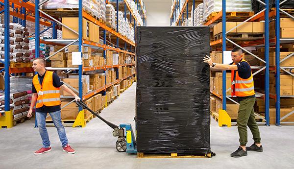 Pracownicy magazynu transportujący towar